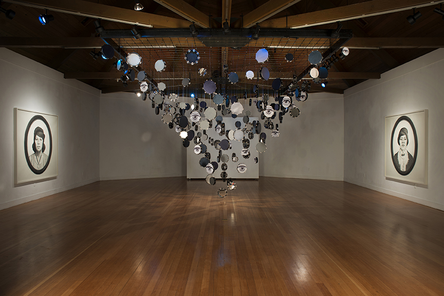 Lava Thomas, Looking Back and Seeing Now, 2015. Site-specific installation including: Tambourine installation, altered tambourines, lambskin, leather, ribbon, acrylic mirrors, digital prints, glue, monofilament wire, s-hooks, wood, and steel, 15 x 12 x 20 ft.; Looking Back 1. Graphite, conté pencil, charcoal, and watercolor on paper. 72 x 72 in.; Looking Back 2. Graphite, conté pencil, charcoal, and watercolor on paper. 72 x 72 in.